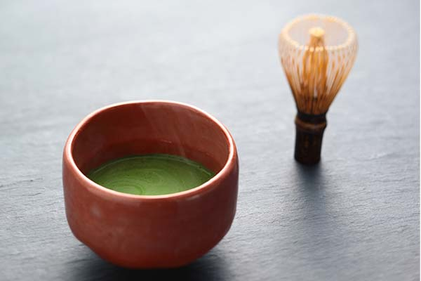 matcha latte with wisk for frothing